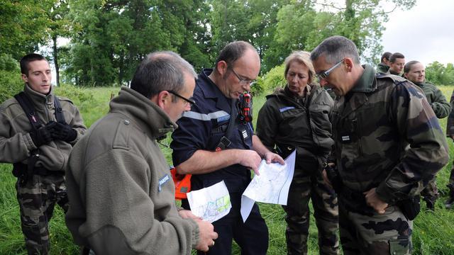 Des gendarmes consultent des cartes lors d'une opération de recherches le 25 mai 2013 près de Moragne, pour retrouver Sydney [Xavier Leoty / AFP]
