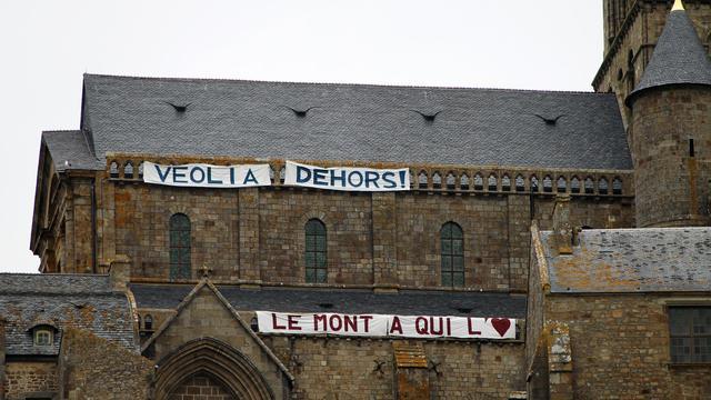 Une photo du 10 juin 2013 montre des banderoles de protestation déployées sur l'abbaye du Mont-Saint-Michel [Charly Triballeau / AFP]