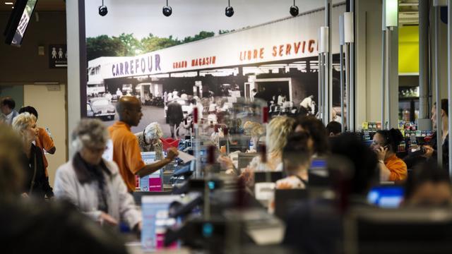 Des clients paient à l'hypermarché Carrefour de Sainte-Geneviève-des-Bois, le 14 juin 2013 [Fred Dufour / AFP]