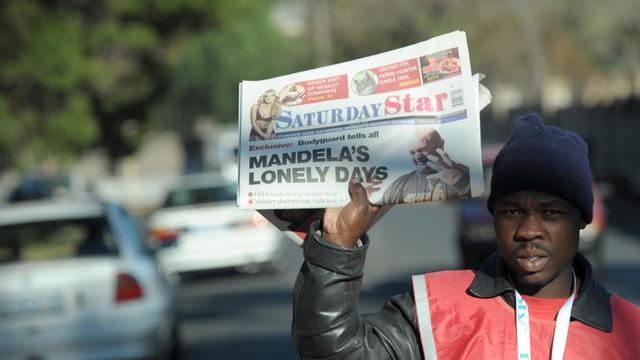 """Un vendeur de journaux à Johannesbourg, le 15 juin 2013 brandit le Saturday Star titrant: """"Les journées solitaires de Mandela"""" [Alexander Joe / AFP]"""