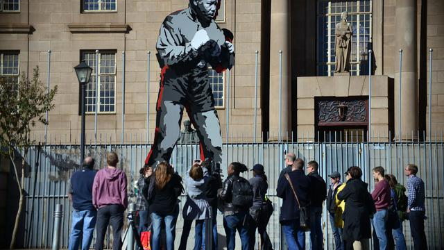 Des touristes autour d'une statue de Nelson Mandela représenté en boxeur le 15 juin 2013 à Johannesburg [Mujahid Safodien / AFP]