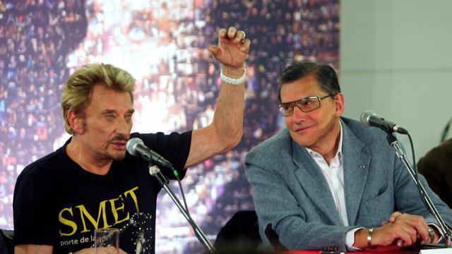 Johnny Hallyday et son producteur de l'époque, Jean-Claude Camus, lors d'une conférence de presse à Paris le 31 mai 2006 [Jacques Demarthon / AFP/Archives]