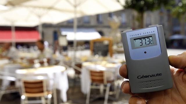 Un restaurateur relève a l'aide d'un thermomètre la température sur la terrasse de son établissement, le 17 juillet 2006 à Bordeaux, [Patrick Bernard / AFP/Archives]