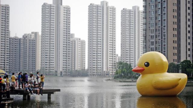 Des personnes prennent des photos le 1er juin 2013 d'un canard en plastique géant sur un plan d'eau à Tianjin, dans l'est de la Chine [ / AFP]