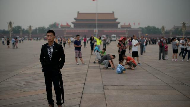Un policier en civil (G) suit des journalistes sur la place Tiananmen à Pékin le 4 juin 2013 [Ed Jones / AFP]