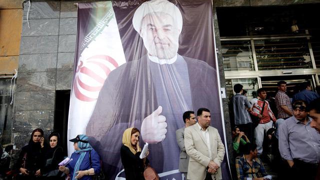 Des Iraniens rassemblés devant un portrait géant de Rohani, le 15 juin 2013 à Téhéran [Behrouz Mehri / AFP]