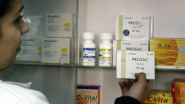 Une pharmacienne montrant des médicaments utilisés pour combattre la dépression