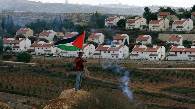 Un protestataire palestinien face à une colonie israélienne