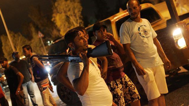Un Libyen brandit son arme en signe de victoire devant la caserne en feu du groupe salafiste d'Ansar al-Charia, à Benghazi, le 21 septembre 2012.