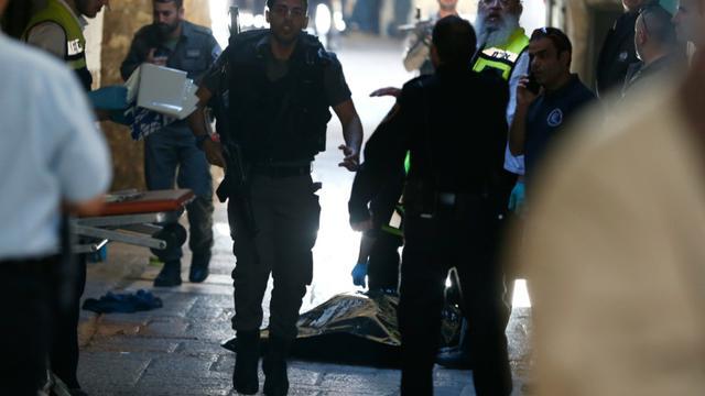 Des membres des forces de sécurité et du personnel médical israéliens près du corps de l'assaillant palestinien tué après qu'il eut blessé au couteau un garde-frontière israélien dans la vieille ville de Jérusalem, le 29 novembre 2015 [AHMAD GHARABLI / AFP]