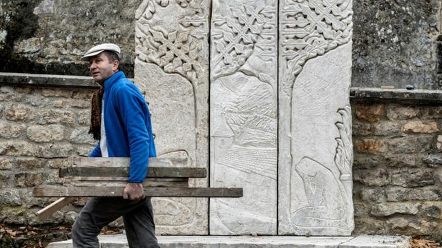Un employé municipal passe devant le nouveau monument aux morts de Parigny-la-Rose, dans le centre de la France, le 9 novembre 2015 [JEFF PACHOUD / AFP]