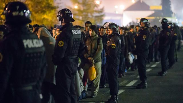 Des policiers slovènes encadrent les migrants sur le point de monter dans un bus le 28 octobre 2015 à Sentilj  [Rene Gomolj / AFP]
