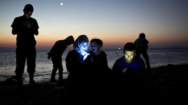 Des migrants consultent leur téléphone portable laors qu'ils viennent d'accoster avec leur embarcation de fortune sur une plage de l'île grecque de Kos, le 12 août 2015 [Angelos Tzortzinis / AFP/Archives]