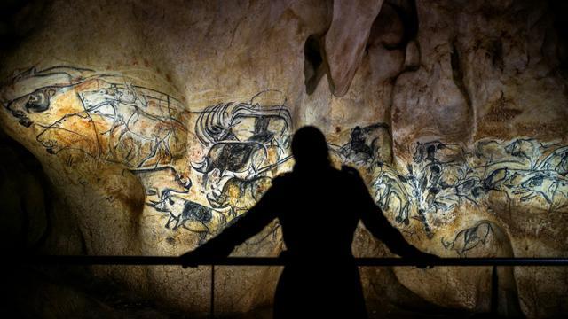 Une personne observe une reproduction à taille réelle des fresques de la cave Chauvet, à Vallon Pont d'Arc le 8 avril 2015 [JEFF PACHOUD / AFP/Archives]