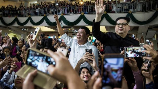 Un sosie du président philippin Rodrigo Duterte et celui du numéro-un nord-coréen Kim Jong Un ont suscité étonnement et stupeur lors d'un service religieux à Hong Kong, le 3 février 2019. [ISAAC LAWRENCE / AFP]