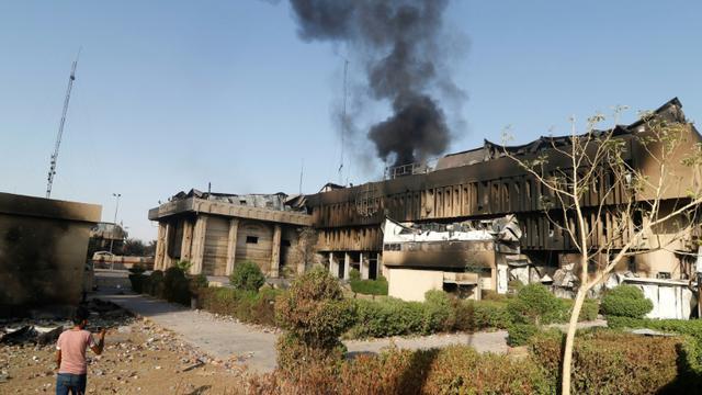 De la fumée s'élève le 7 septembre 2018  du siège du gouvernorat provincial à Bassora incendié ces derniers jours lors de manifestations [Haidar MOHAMMED ALI / AFP]