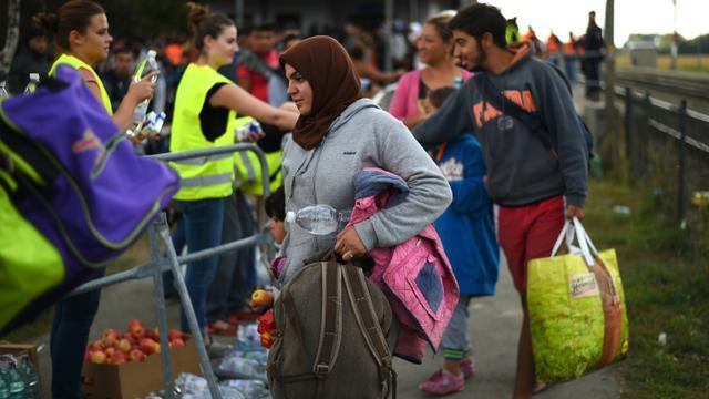 Des migrants embarquent à bord d'un bus le 10 septembre 2015 à la gare de Nickelsdorf en Autriche à la frontière avec la Hongrie [JOE KLAMAR / AFP]
