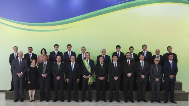 Le président brésilien Jair Bolsonaro, ceint de l'écharpe présidentielle, entouré de ses ministres, au palais du Planalto à Brasilia, le 1er janvier 2019 [Sergio LIMA / AFP]