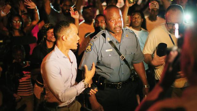 Le capitaine Ron Johnson chargé de ramener l'ordre à Ferguson marche parmi les manifestants, le 14 août 2014 dans cette petite ville du Missouri [Scott Olson / Getty Images North America/AFP]