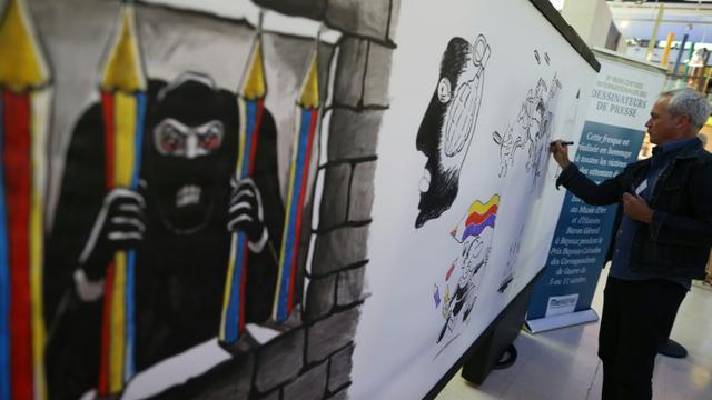"""Le dessinateur britannique Ant fait une caricature sur un """"tableau de la liberté d'expression"""" le 11 septembre pendant les 5èmes rencontres internationales des dessinateurs de presse du Mémorial de Caen [Charly Triballeau / AFP]"""