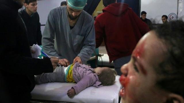 Des médecins syriens examinent une enfant dans un hôpital de fortune après des bombardements du régime syrien sur la ville de Douma dans la Ghouta orientale, le 22 février 2018 [Hamza AL-AJWEH / AFP]