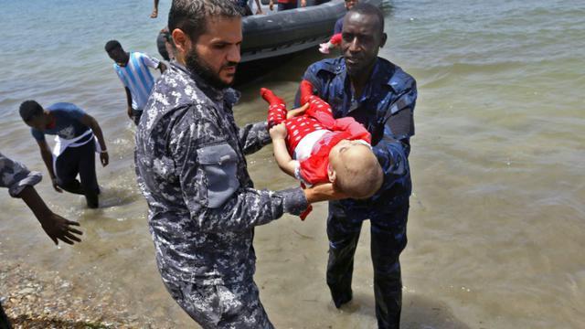 Le corps d'un des trois bénés repêchés vendredi après le naufrage d'une embarcation est porté par des membres des forces de sécurité libyennes, le 29 juin 2018 à al-Hmidiya [Mahmud TURKIA / AFP]