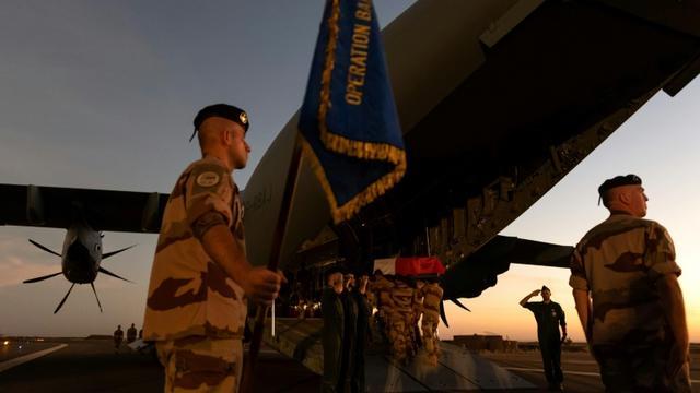 """Les cercueils recouverts du drapeau aux couleurs de la France, près d'un soldat brandissant un étendard portant la mention """"Opération Barkhane"""", avant d'être embarqués dans le gros porteur. Photo prise le 30 novembre 2019 et fournie le 1er... [THOMAS PAUDELEUX / ECPAD/AFP]"""