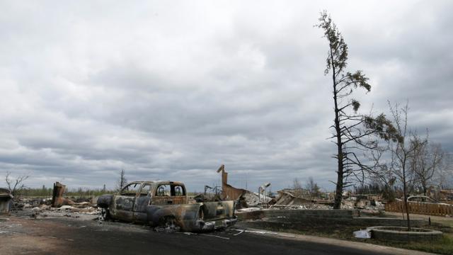 Des véhicules et des maisons incendiés dans le quartier de Beacon Hill à Fort McMurray le 9 mai 2016 [CHRIS WATTIE / POOL/AFP/Archives]