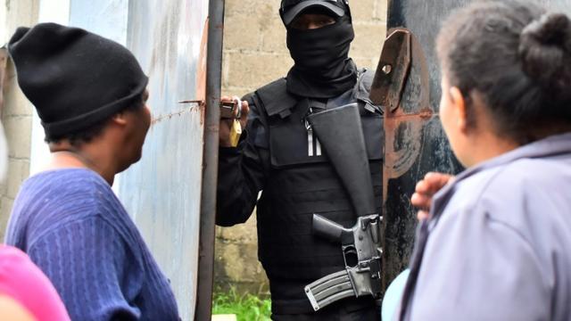 Des parents de détenus demandent des nouvelles de leurs proches à un policier devant la prison de Tela après des affrontements meurtriers, le 21 décembre 2019 [STR / AFP]