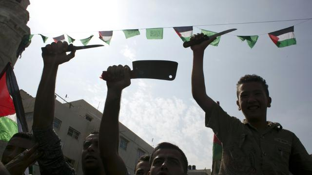 Des étudiants palestiniens brandissent des couteaux en guise de menaces contre les Israéliens, le 18 octobre 2015 à Khan Yunis, dans la bande de Gaza [SAID KHATIB / AFP]