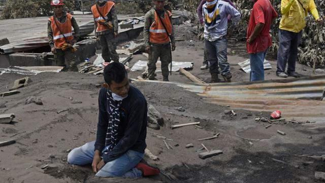 Un homme pleure devant sa maison ensevellie de cendres les membres de sa famille disparus, le 7 juin 2018 à Escuintla [JOHAN ORDONEZ / AFP]
