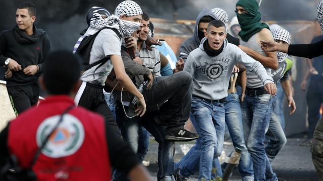 Un Palestinien lanceur de pierre est porté par des camarades après avoir été blessé lors de heurts avec les forces israéliennes à Beit El près de Ramallah le 9 octobre 2015 [Abbas Momani / AFP]