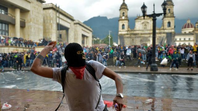 Un manifestant lançant une pierre contre la police, le 21 novembre 2019 à Bogota. [RAUL ARBOLEDA / AFP]
