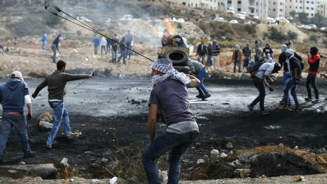 Des Palestiniens lancent des pierres vers des soldats israéliens dans les environs de Ramallah, le 27 octobre 2015 [ABBAS MOMANI / AFP/Archives]