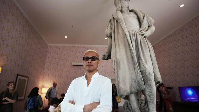 L'artiste Tatzu Nishi pose le 20 septembre 2012 devant la statue de Christophe Colomb, autour de laquelle il a construit un appartement à Colombus Circle à New York [Spencer Platt / Getty Images/AFP]