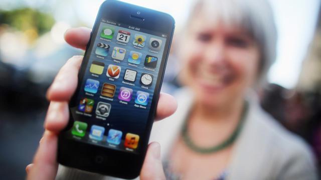 """Une femme tend l""""iPhone 5, le 21 septembre 2012 à New York [Mario Tama / Getty Images/AFP]"""