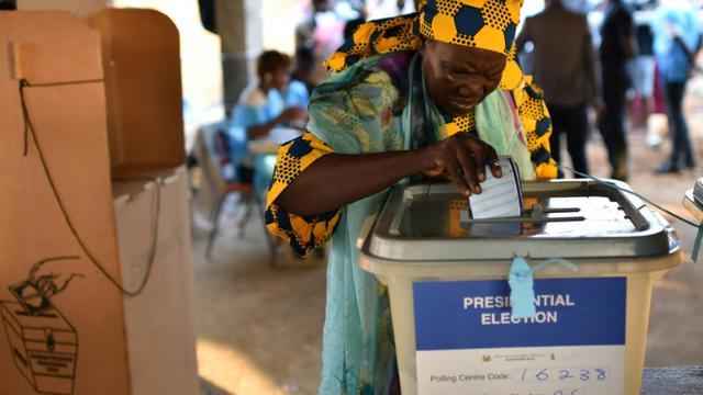 Une femme glisse son bulletin dans l'urne lors des élections générales au Sierra Leone, le 7 mars 2018 à Freetown [ISSOUF SANOGO / AFP]