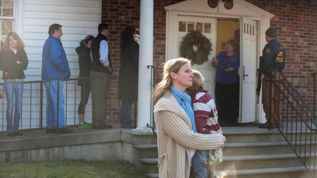 Une femme tient son enfant dans ses bras devant une église de Newton, près des lieux de la fusillade dans une école primaire, le 14 décembre 2012.