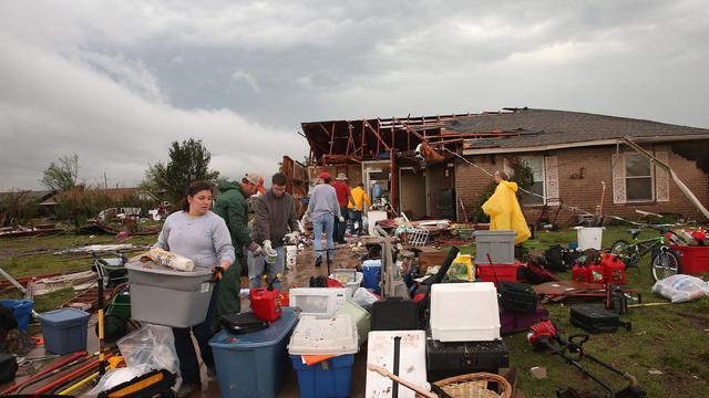 Des bénévoles aident le 23 mai 2013 le propriétaire d'une maison qui a été détruite par la tornade qui s'est abattue sur la ville de Moore, dans l'Oklahoma [Scott Olson / Getty Images/AFP]