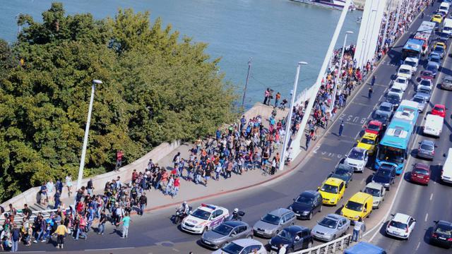 Plus d'un millier de migrants quittent à pied la zone de transit de la gare principale de Budapest pour rejoindre la frontière autrichienne, le 4 Septembre 2015 [Attila Kisbenedek / AFP]