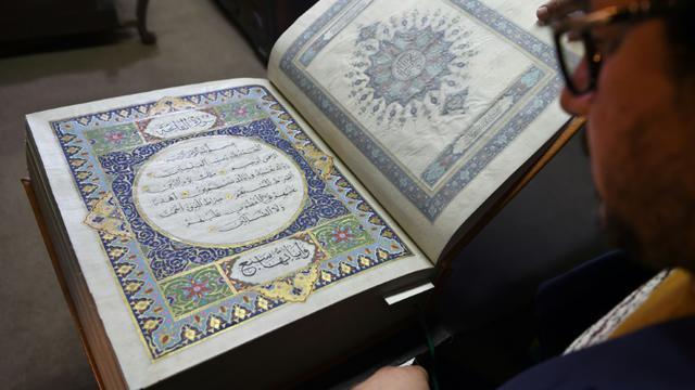 L'Afghan Mohammad Tamim Sahibzada, maître ès miniatures et responsable des enluminures, montre un Coran en soie dans les 610 pages ont été peintes à la main, le 19 avril 2018 à la Fondation britannique Turquoise Mountain, à Kaboul [WAKIL KOHSAR / AFP]