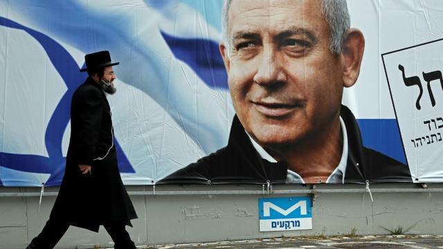 Un orthodoxe juif marche devant une affiche électorale du Premier ministre israélien Benjamin Netanyahu, le 1er avril 2019 à Jérusalem [THOMAS COEX / AFP/Archives]