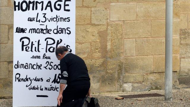 Un homme s'agenouille devant l'affiche appellant à un hommage aux victimes de la collision de Puisseguin le 24 octobre 2015 à Petit-Palais [JEAN-PIERRE MULLER / AFP]