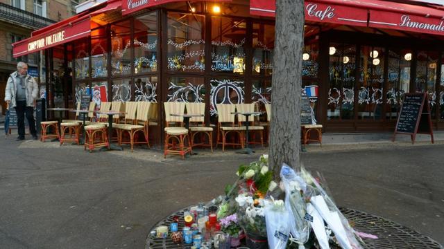"""Bouquets de fleurs déposés au pied d'un arbre devant le """"Comptoir Voltaire"""" le 16 décembre 2015 à Paris [BERTRAND GUAY / AFP]"""