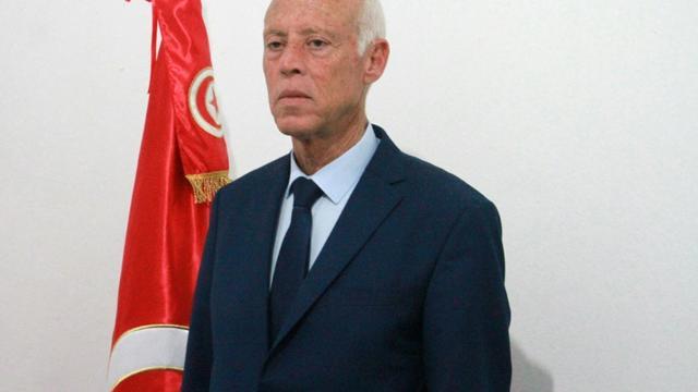 Le candidat indépendant à la présidentielle Kais Saied pose devant le drapeau tunisien, le 15 septembre 2019 à Tunis [MOHAMED KHALIL / AFP]