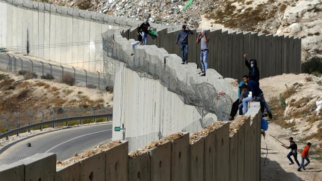 Des Palestiniens debout sur le mur séparant la ville d'Abu Dis en Cisjordanie et Jérusalem est le 28 octobre 2015 [Ahmad Gharabli / AFP/Archives]