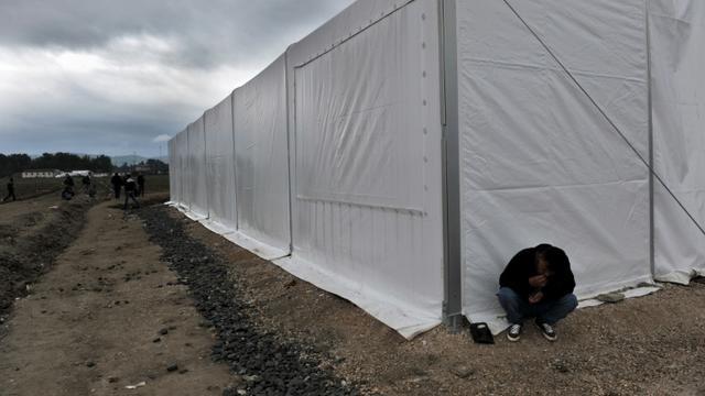 Un homme assis devant une tente d'un camp de migrants près de la  frontière entre la Grèce et la Macédoine à Idomeni, le 14 octobre 2015  [STR / AFP]