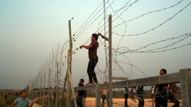 Des Palestiniens s'attaquent aux barbelés à la frontière entre Gaza et Israël, lors d'affrontements avec les forces de l'ordre israéliennes le 12 octobre 2015 [MOHAMMED ABED / AFP]