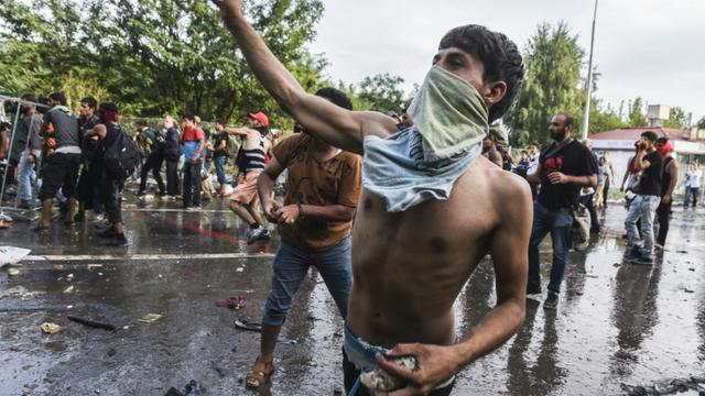 Des migrants lancent des pierres contre les forces antiémeutes hongroises, le 16 septembre 2015 près de Horgos, à la frontière avec la Serbie [ARMEND NIMANI / AFP]
