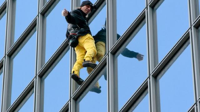 """Le """"Spiderman français"""", Alain Robert, escalade à mains nues la tour Total du quartier d'affaires de la Défense, le 21 mars 2016 [JACQUES DEMARTHON / AFP]"""